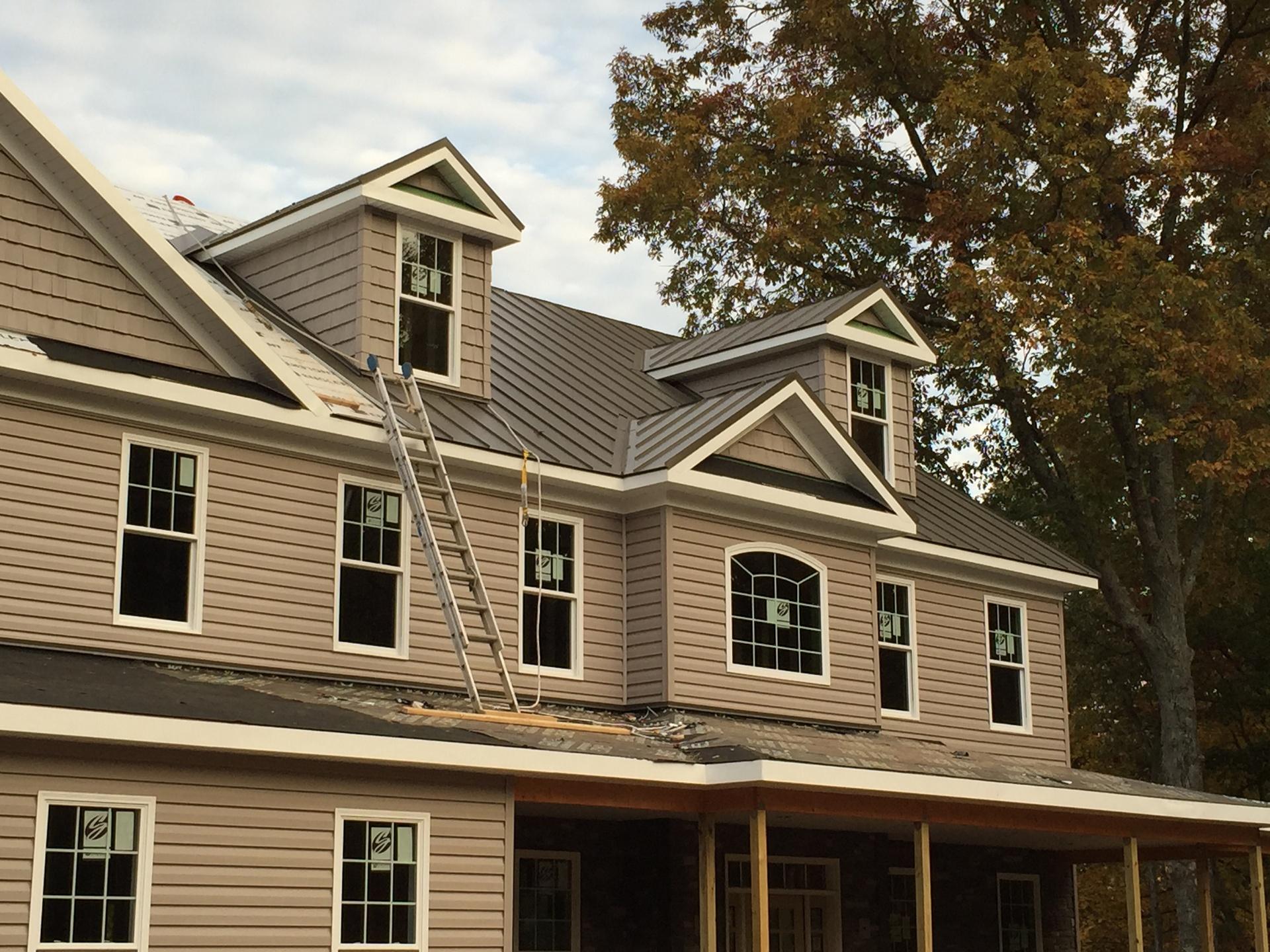 standing seam metal roof being installed